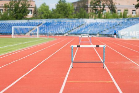 hurdling: Stadium treadmill.Photo treadmill with a barrier in an empty stadium during the day