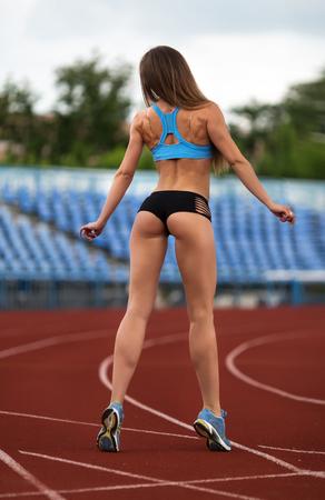 posing: Sexy fitness.Female model posing at the stadium