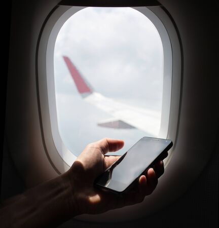 flight mode: hand holding mobile phone with flight mode in the airplane