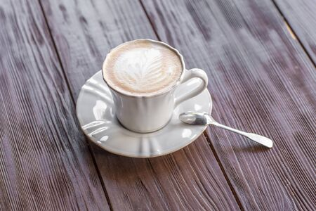cappuccino cup: Cup of Cappuccino on wooden slat table Stock Photo