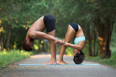 Acro yoga, two sporty people practice yoga in pair, couple doing stretching exercise in the garden Imagens