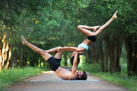 Acro yoga, two sporty people practice yoga in pair, couple doing stretching exercise in the garden 版權商用圖片