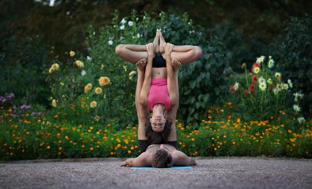 position d amour: Acro yoga, deux personnes sportives pratiquent le yoga dans la paire, en couple faisant exercice d'étirement dans le jardin.