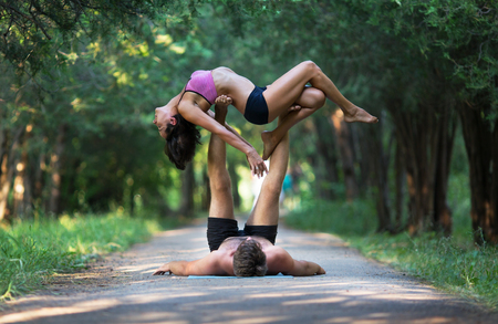 haciendo ejercicio: Acro yoga, two sporty people practice yoga in pair, couple doing stretching exercise in the garden Foto de archivo