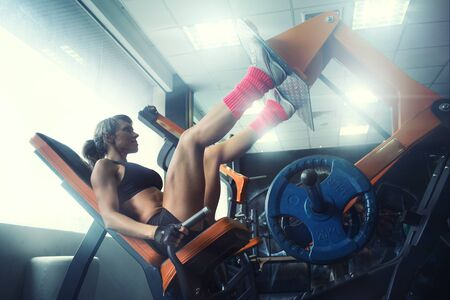 perseverance: woman flexing muscles on leg press machine in the gym