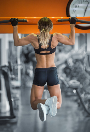 pull up: woman doing  lifting up on the gym bar Stock Photo