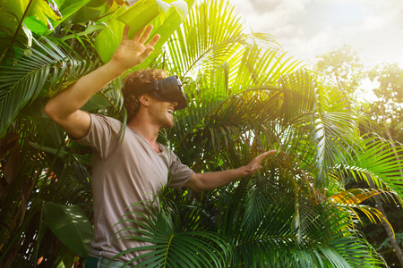 man in gray T-shirt, virtual reality 3D headset and exploring the play on a background of nature jungle