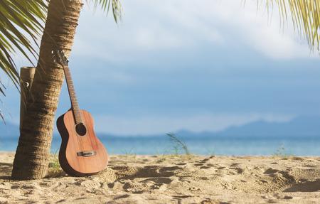 ヤシの木の下で砂浜でアコースティック ギターの立っています。 写真素材