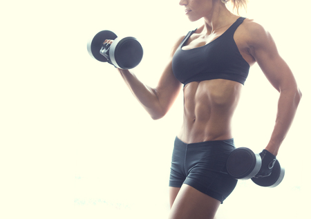 Muscular fitness woman posing with dumbbels on white background