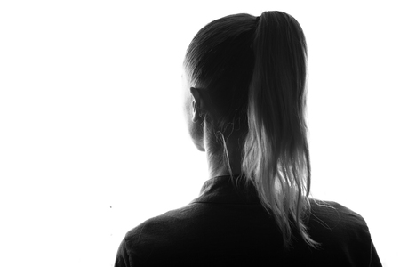 Female person silhouette,view from behind,back lit over white Stock Photo