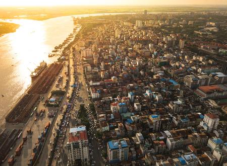 Toma aérea, vista desde el avión no tripulado en el cruce de carreteras y la ciudad de Yangon, cerca del río Rangoon al atardecer colores, Myanmar Foto de archivo - 99738893