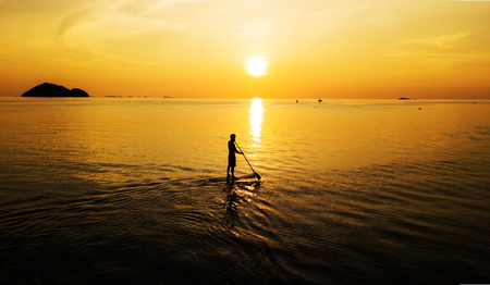 Aerial: Sunset silhouette of a person standing up at paddle board on vacation in Thailand