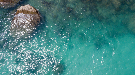 Aerial: overhead  view of transparent green foaming  waves against the rocky line and bottom