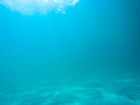 Underwater scene with sunlight through water surface to bottom of sand side