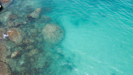 Aerial: overhead  view of transparent green foaming  waves against the rocky line and bottom 写真素材 - 100263323