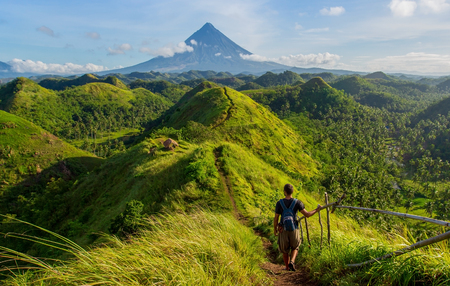 Hiker with backpack looks at the view on the Mayon volcano,Quit in Day Hills area,Philippines Imagens