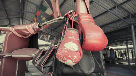 A pair of old Muay Thai boxing gloves hangs on the boxing ring at training  camp Imagens