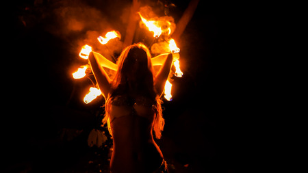 Fire woman dancing with burning fans