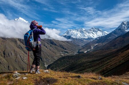 Active hiker hiking, enjoying the view, looking at mount Everest and use use mobile phone