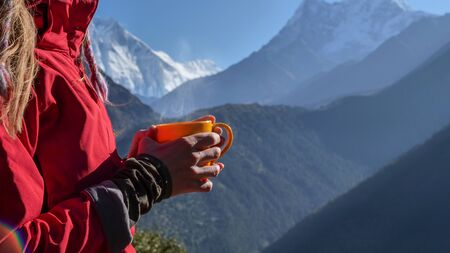 Woman with cup of hot drink, enjoying the view, looking at Himalaya mountains landscape. Travel sport lifestyle concept 写真素材
