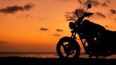 Motorcycle silhouette at sunset time near sea coast line Archivio Fotografico