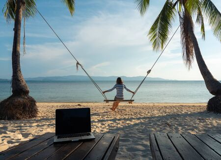 Woman after freelance work on the swing at tropical island sand beach line