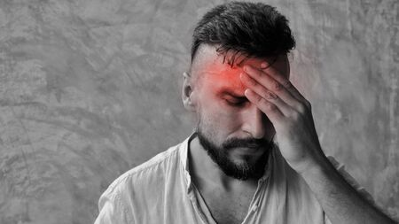 A man suffering headache from a painful head pain and looking tired, worried and stressful