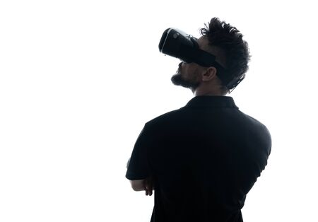 Man in dark T-shirt wearing virtual reality 3D headset and exploring the play