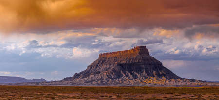 barren land: Factory Butte is the most recognizable feature of a large area of stark, barren land either side of the Fremont River known as the Upper Blue Hills, bordered by Capitol Reef to the west, the Henry Mountains to the south, San Rafael Swell to the north and  Stock Photo