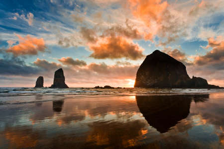 horizon reflection: Quiet summer sunset at Cannon Beach, Oregon, USA: colorful clouds, sky reflection in the water.