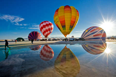 Reflection of the colorful hot air balloons preparing for ascend in the White Sands National Monument, New Mexico, USA
