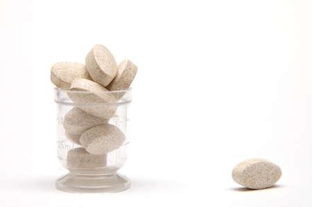 ingest: Dose of pills on white Stock Photo
