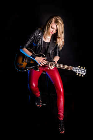 Enigmatic, stylish blonde girl guitarist plays by electric guitar in leather jacket. Woman teacher shows how to play song. Female musician rock star on black background. Rebel, rocker
