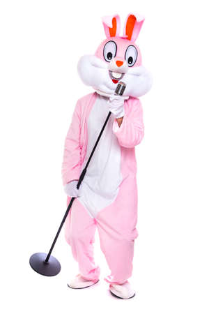 Life size stuffed easter bunny sings in retro microphone, celebrates easter, dances on white background. Funny, happy singer, musician, rabbit or hare having fun