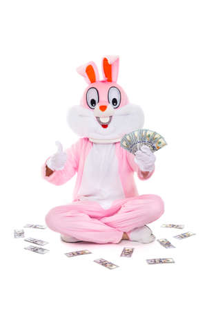 Easter bunny rabbit with fan of dollars, celebrates easter. Rich lucky man holds money hundred dollar bills