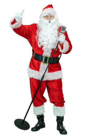 Santa holds retro microphone, sings song, shows index finger. Santa Claus is singing to elvis microphone, showing finger on white background. Christmas coming