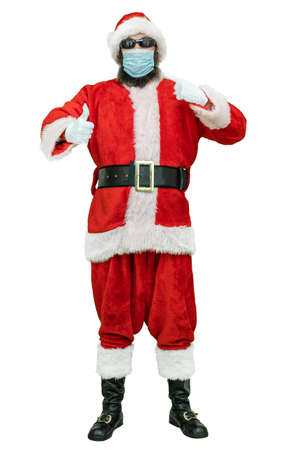 Santa wear in a covid medical mask, throws thumb index finger up. Christmas coming