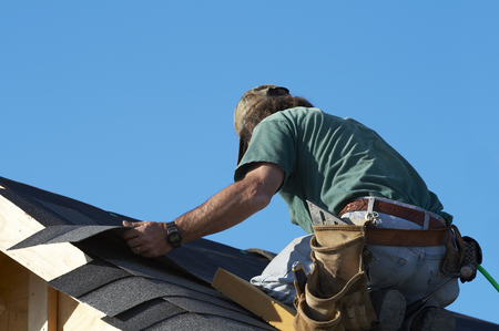 roof shingles: worker on roof putting shingles down Stock Photo