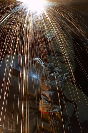 laboring: one welder working at night and sparks flying
