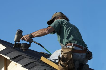 roof shingles: a roofer on a roof putting down shingles