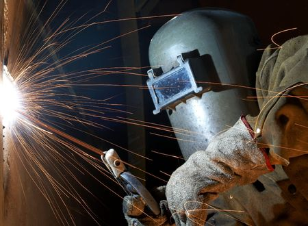 a welder working at shipyard at night photo