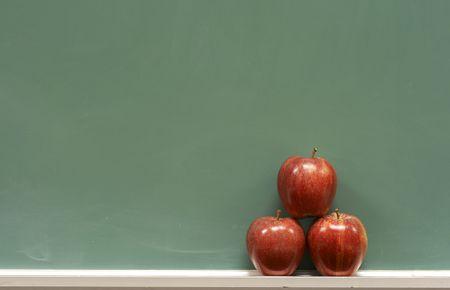 red apples on chalkboard in school classroom