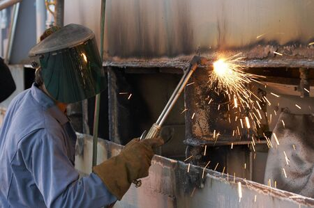 a worker using a torch to burn steel