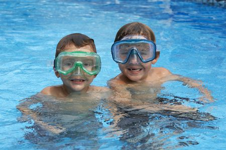 two young boys in pool with goggles on