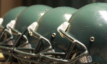 facemask: a macro of few football helmet on bench