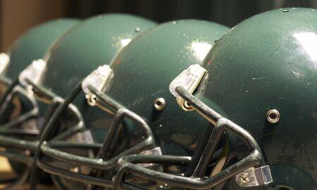a macro of few football helmet on bench