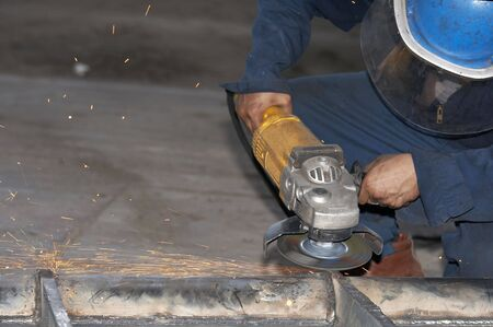 a picture of a worker grinding steel photo