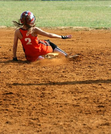 a fastpitch softball player sliding into second base