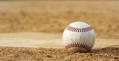 spring training: one baseball on home plate at a sports field
