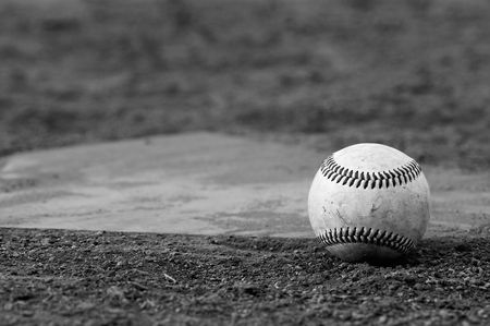 one baseball on home plate at a sports field photo